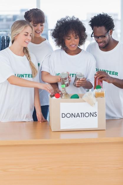 Vrijwilligers die voedsel in giftdoos zetten Premium Foto
