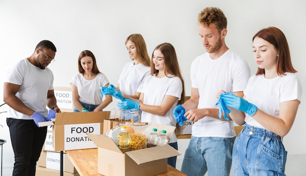 Vrijwilligers met handschoenen die voedsel bereiden voor donatie Gratis Foto
