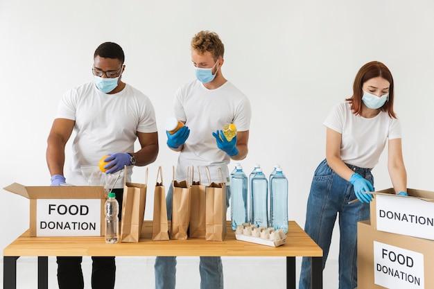 Vrijwilligers met handschoenen en medische maskers bereiden van voedsel voor donatie met dozen Gratis Foto