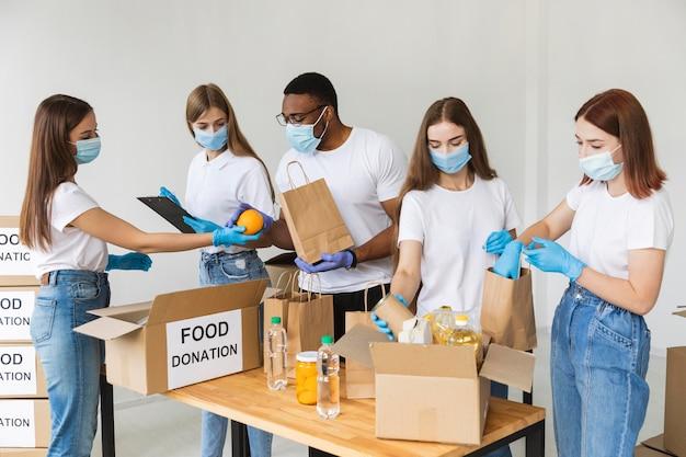 Vrijwilligers met handschoenen en medische maskers bereiden van voedsel voor donatie Premium Foto