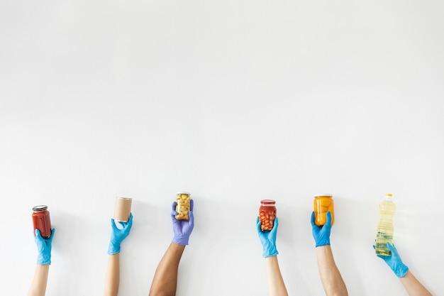 Vrijwilligershanden met handschoenen met proviand voor donatie Gratis Foto