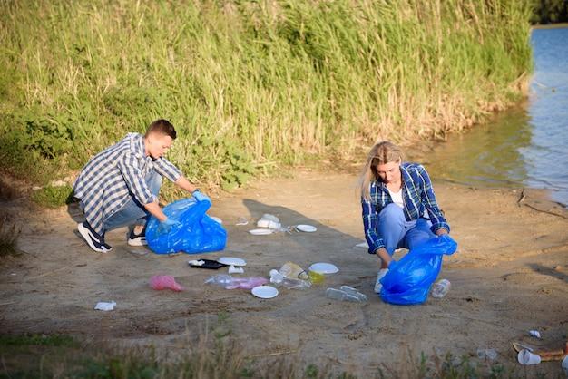 Vrijwilligersmens die afval op het strand verzamelt. ecologie concept. Premium Foto