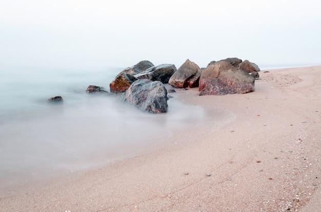 Vroege ochtend op de rotsachtige kust van de zee. glad water van de zee vanwege lange blootstelling. tijd pre zonsopgang. Premium Foto
