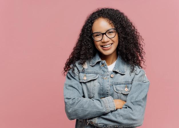 Vrolijk, aangenaam ogend vrouwelijk model draagt een optische bril en een jeansjack, houdt de armen over de borst gevouwen Premium Foto