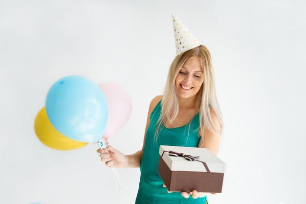 Vrolijk blondemeisje in verjaardagshoed Gratis Foto