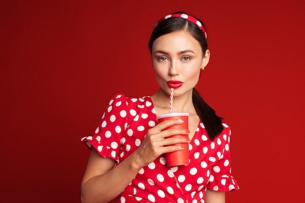 Vrolijk donkerbruin pin-up meisje dat frisdrank houdt Premium Foto