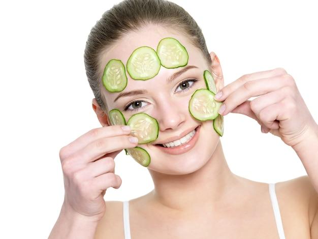 Vrolijk gelukkig mooi meisje gezichtsmasker van komkommer geïsoleerd op wit toe te passen Gratis Foto