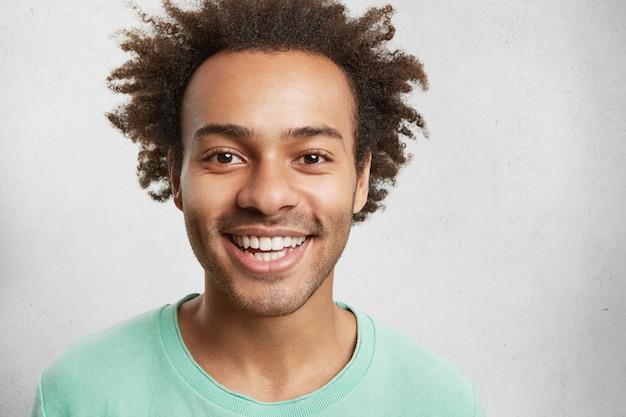 Vrolijk gemengd ras mannetje met borstelharen, borstelig kapsel en witte perfecte tanden, heeft een goed humeur Gratis Foto