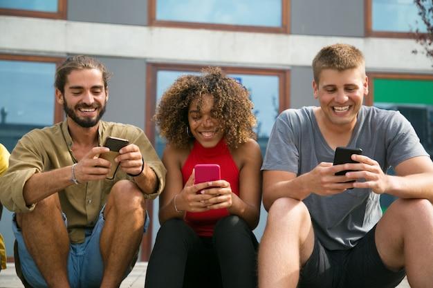 Vrolijk gerichte multi-etnische studenten die hun telefoons gebruiken Gratis Foto
