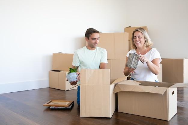 Vrolijk getrouwd stel verhuizen naar een nieuw appartement, dingen uitpakken, op de vloer zitten en voorwerpen uit open dozen halen Gratis Foto