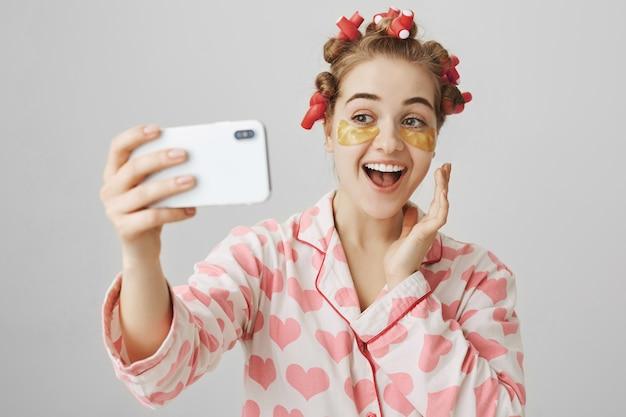 Vrolijk glimlachend meisje in haarkrulspelden en ooglapjes die selfie nemen die nachtkleding dragen Gratis Foto