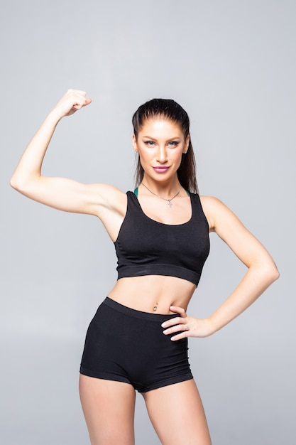 Vrolijk glimlachend sportieve vrouw demonstreren biceps, geïsoleerd Gratis Foto