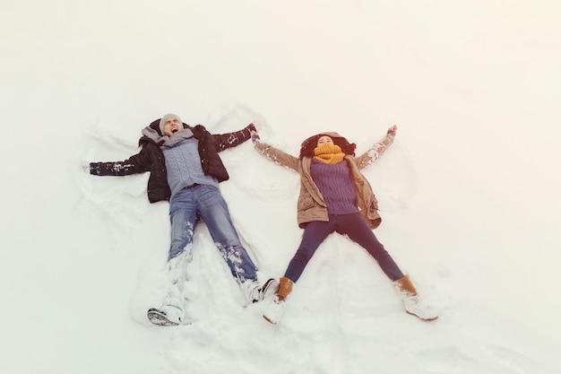Vrolijk jong paar dat in een de winterdag loopt Gratis Foto