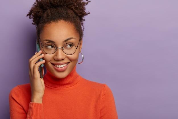 Vrolijk jong vrouwelijk meisje met een donkere huid heeft een mobiel telefoongesprek, draagt een ronde transparante bril, heeft een charmante glimlach, hoort goed nieuws, geïsoleerd over de paarse studiomuur, kopieer ruimte Gratis Foto