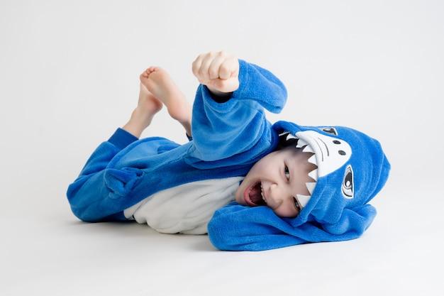 Vrolijk jongetje die zich voordeed op een witte achtergrond in pyjama, blauw haaikostuum Premium Foto