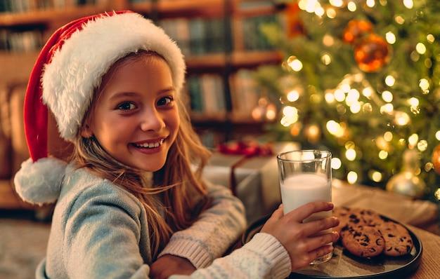 Vrolijk kerstfeest en een gelukkig nieuwjaar! charmant klein meisje santa voorbereid een glas melk en koekjes. Premium Foto