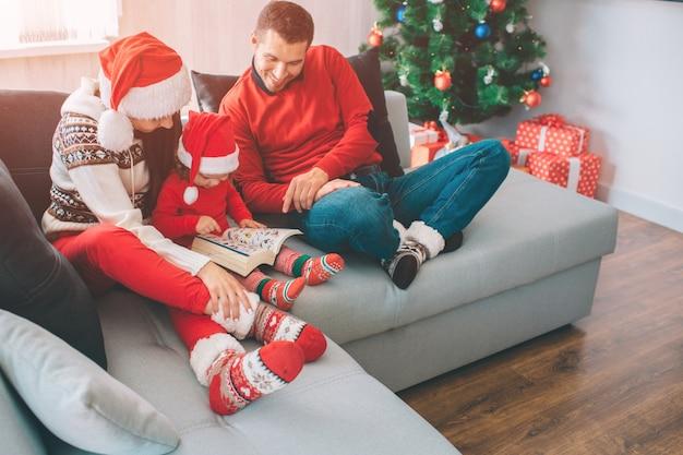 Vrolijk kerstfeest en een gelukkig nieuwjaar. familiezitting samen op bank. klein meisje zit tussen haar ouders in. ze houdt en kijkt naar boek met foto's. de mens kijkt het en glimlacht. zij zijn blij. Premium Foto