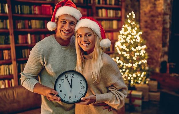 Vrolijk kerstfeest en een gelukkig nieuwjaar! jong koppel met klok in hun handen lachend vijf minuten tot het nieuwe jaar. Premium Foto