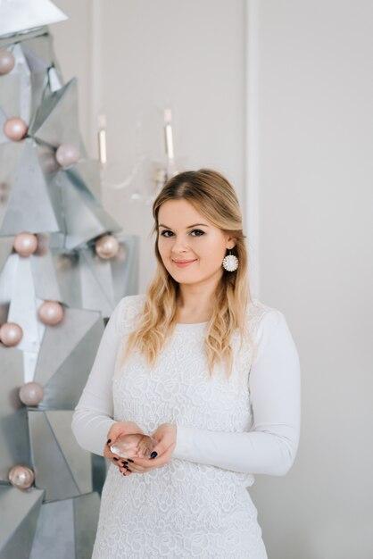 Vrolijk kerstfeest en een gelukkig nieuwjaar. mooi meisje in de buurt van moderne zilveren metalen kerstboom Premium Foto