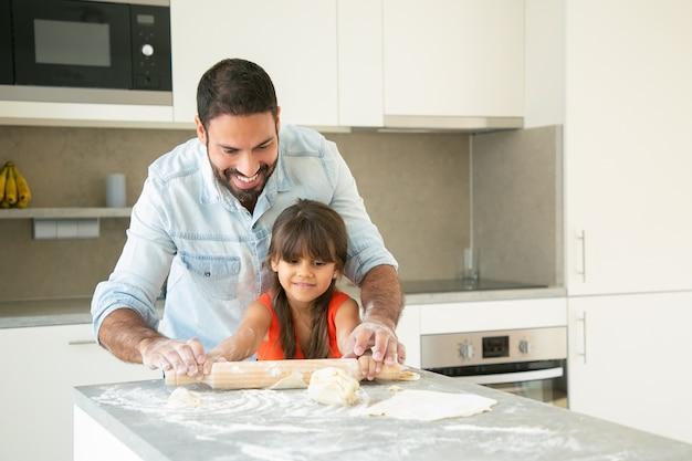 Vrolijk latijns meisje en haar vader die deeg op keukentafel met bloempoeder rollen en kneden. Gratis Foto