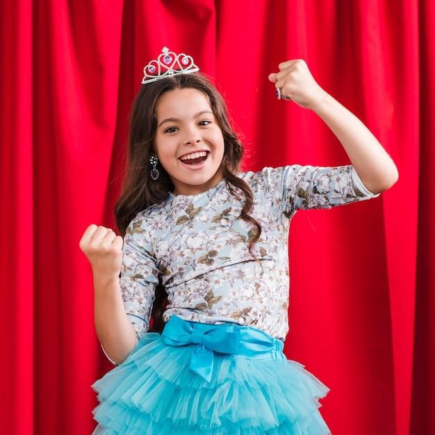 vrolijk leuk meisje die winnaargebaar maken die zich voor rood gordijn bevinden gratis foto
