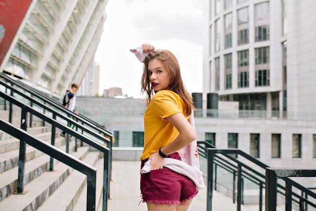 Vrolijk meisje in lichte kleding kijkt over de schouder met belangstelling lopen op stedelijke straat Gratis Foto