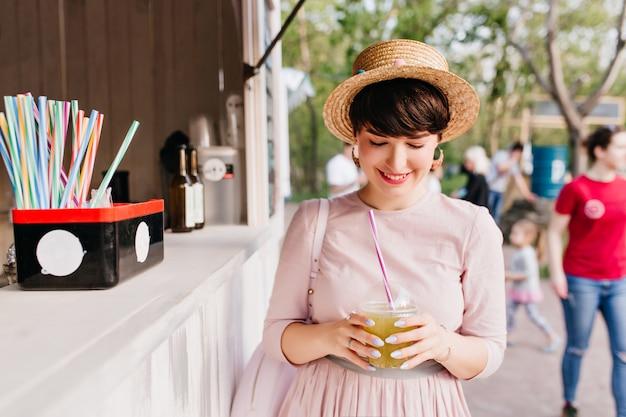 Vrolijk meisje in strohoed kocht een koud drankje, lopend langs het stadsplein Gratis Foto