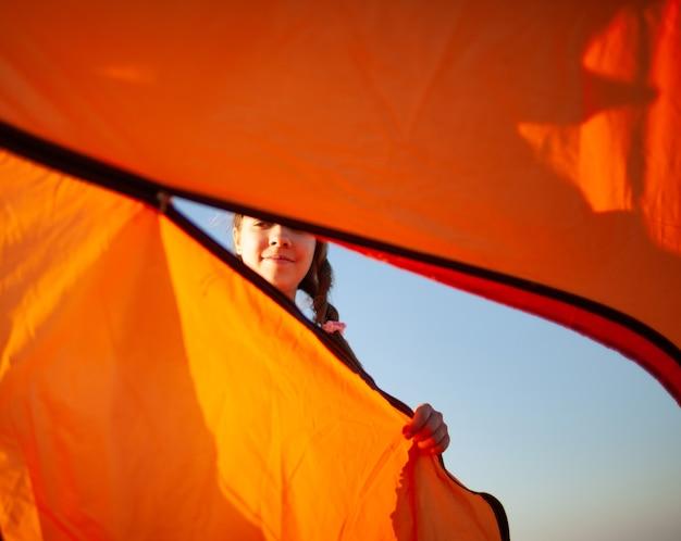 Vrolijk meisje met donker sluit een lichte tent kijken naar haar voorzichtige acties op de blauwe kust op een mooie avond Premium Foto