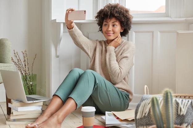 Vrolijk meisje met donkere huid draagt een warme trui en een modieuze broek Gratis Foto