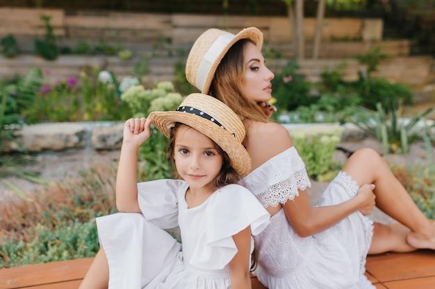 Vrolijk meisje met grote ogen, zittend naast peinzende jonge moeder in romantische witte kleding. ernstige langharige vrouw poseren rijtjes met dochter met bloemen. Gratis Foto
