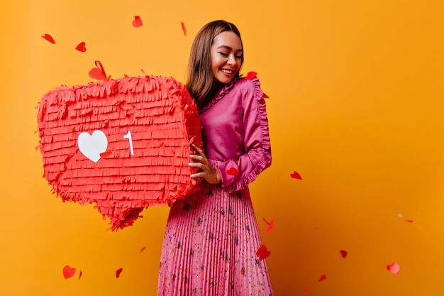 Vrolijk meisje met mooie glimlach poseren met rode bunner. verfijnde brunette vrouwelijke blogger in goed humeur. Gratis Foto