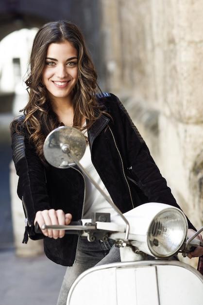 Vrolijk meisje rijdt op een witte scooter Gratis Foto