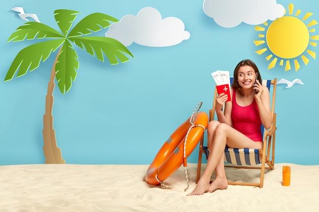 Vrolijk meisje zonnebaadt op het strand, poses op de ligstoel, spreekt via mobiele telefoon, paspoort met kaartjes houdt, geniet van zomervakantie Gratis Foto
