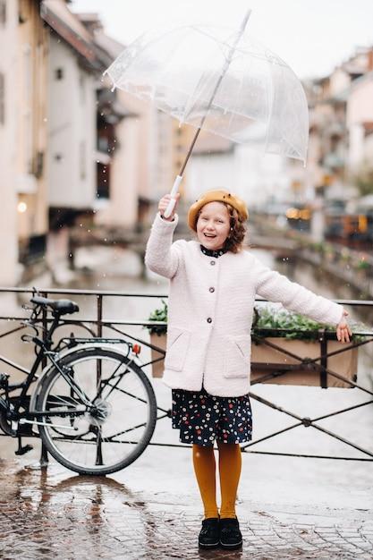 Vrolijk mooi meisje in een jas met een doorzichtige paraplu in annecy Premium Foto