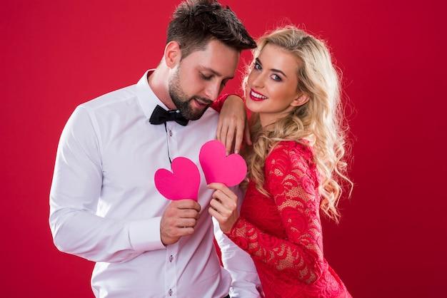 Vrolijk paar dat roze document harten houdt Gratis Foto