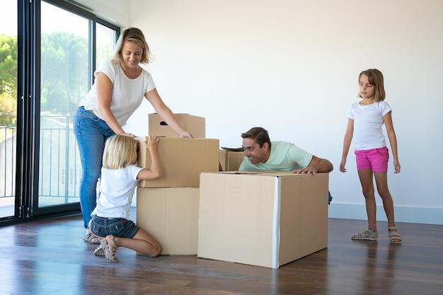 Vrolijk paar ouders en twee meisjes die plezier hebben tijdens het openen van dozen en het uitpakken van dingen in hun nieuwe lege flat Gratis Foto