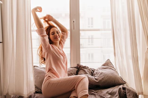 Vrolijk roodharig meisje in pyjama die in ochtend glimlacht. vrolijke gember vrouw poseren in bed. Gratis Foto