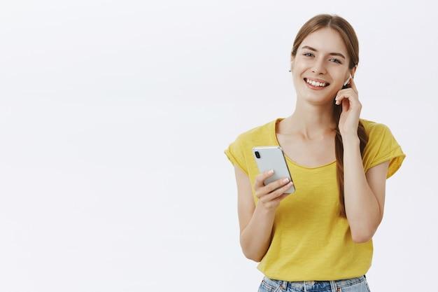 Vrolijk vrij jong meisje luisteren muziek in draadloze oortelefoons, smartphone, genieten van podcast te houden Gratis Foto