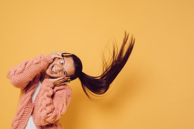 Vrolijke aantrekkelijke brunette in glazen en koptelefoon gekleed in roze trui witte blouse schudt haar hoofd met lang golvend haar tijdens het dansen, over gele achtergrond. positief mensenconcept. Premium Foto