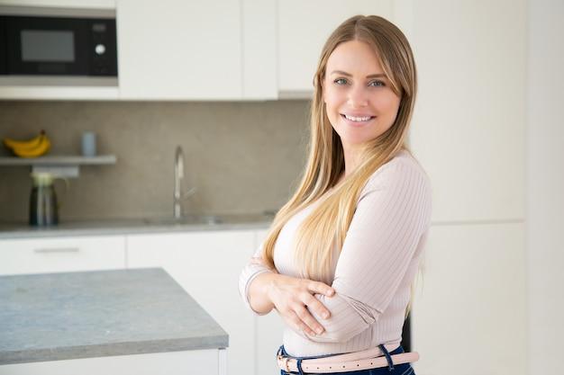 Vrolijke aantrekkelijke eerlijke haired jonge vrouw poseren met armen gevouwen in de keuken Gratis Foto
