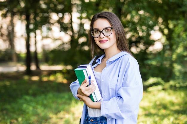 Vrolijke aantrekkelijke jonge vrouw met boeken die en in park staan glimlachen Gratis Foto