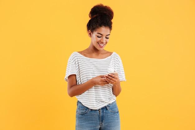 Vrolijke afrikaanse dame die en geïsoleerde telefoon gebruiken typen Gratis Foto