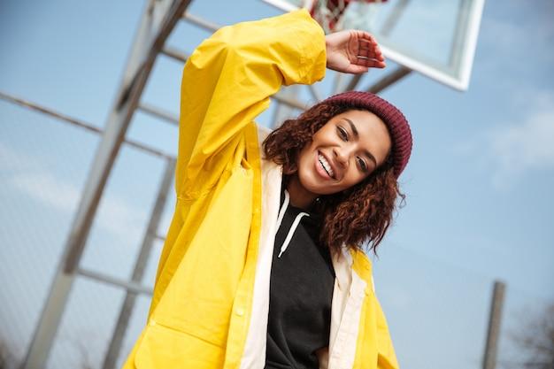 Vrolijke afrikaanse krullende jonge dame die gele laag draagt Gratis Foto