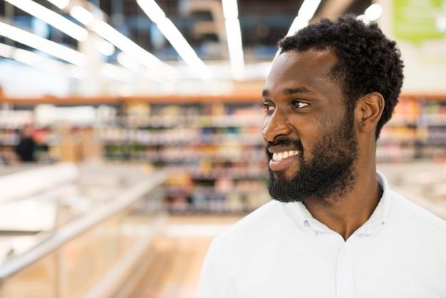 Vrolijke afro-amerikaanse man bij supermarkt Gratis Foto