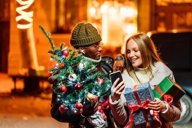Vrolijke afro-amerikaanse man met blanke vrouw die buitenshuis kerstcadeaus online doet Premium Foto