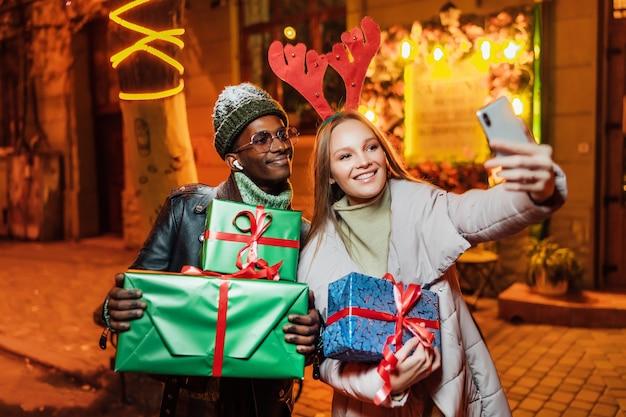 Vrolijke afro-amerikaanse man met blanke vrouw op straat terwijl het nemen van selfie foto op smartphone Premium Foto