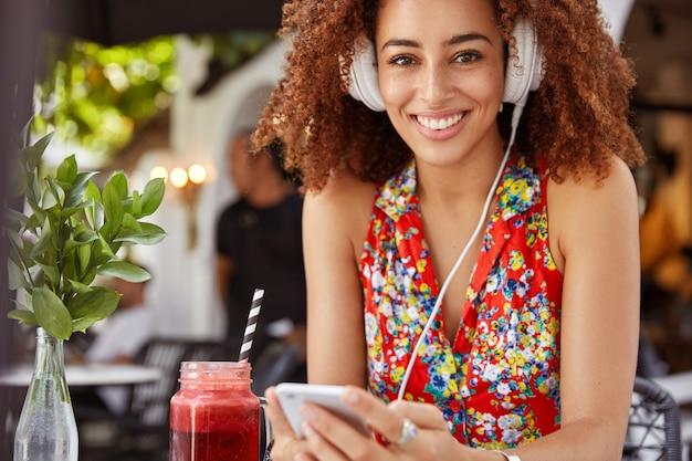 Vrolijke afro-amerikaanse vrouw met krullend haar luistert cool compositie in koptelefoon, geniet van een goede ontspanning en zomerrust in stoeprestaurant met cocktail. Gratis Foto