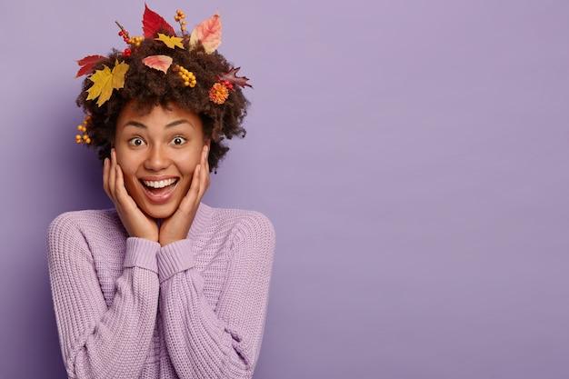 Vrolijke afro-vrouw met krullend haar, raakt de wangen, heeft bladeren in het haar gevallen, draagt een paarse trui, glimlacht breed, poseert over violette muur, vrije ruimte Gratis Foto