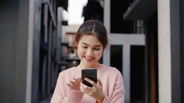 Vrolijke aziatische backpacker blogger vrouw met behulp van smartphone voor richting en kijken op de kaart van de locatie tijdens het reizen op chinatown in peking, china. lifestyle rugzak toeristische reizen vakantie concept. Gratis Foto