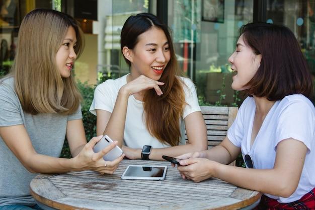 Vrolijke aziatische jonge vrouwen zitten in cafe drinken koffie met vrienden en praten samen Gratis Foto